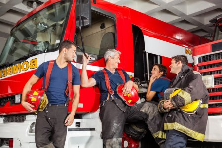 Team of happy firefighters conversing while leanin...