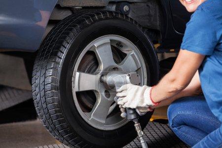 Photo pour Abdomen des femelle mécanicien aide clé pneumatique pour pneu de voiture de fixer à l'atelier de réparation - image libre de droit