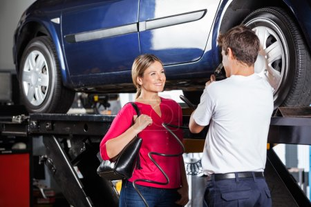 Mechanic Discussing With Customer While Filling Car Tire