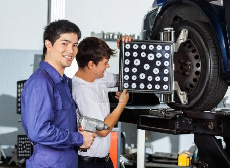 Mechanic With Colleague Using Wheel Aligner On Car