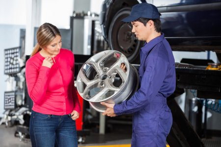 Mechanic Showing Hubcap To Customer