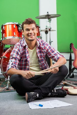Male Drummer Holding Sticks While Sitting On Floor