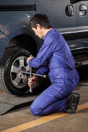Photo pour Vue latérale du pneu de voiture de réparation de mécanicien masculin à l'atelier de réparation automobile - image libre de droit