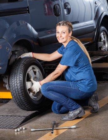 Female Mechanic Fixing Car Tire