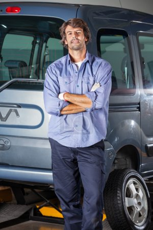 Confident Technician Leaning On Car