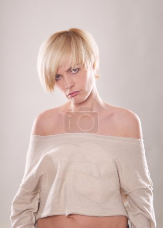 The blond woman with short hair and a beautiful smile with red lips isolated. Touches the lips