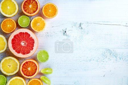 Photo pour Divers agrumes colorés sur fond blanc en bois, vue de dessus - image libre de droit