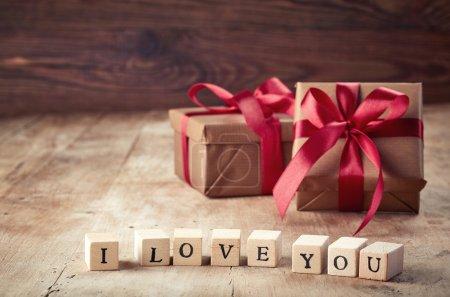 Photo pour Coffrets cadeaux marron et cubes en bois avec texte Je t'aime sur fond en bois - image libre de droit