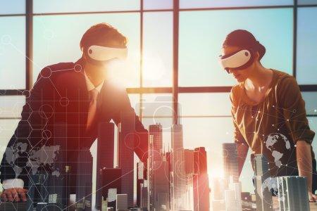Photo pour Deux hommes d'affaires développent un projet en utilisant des lunettes de réalité virtuelle. le concept de technologies du futur - image libre de droit