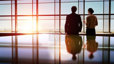 Photo for Team of successful business people. two businessmen resting and talking in the office. man and woman look at the city from the window of the business center - Royalty Free Image