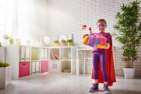 Photo pour Charmante petite assistante. Petite fille mignonne fait le ménage de la maison. Fille est habillé dans un costume Superman . - image libre de droit