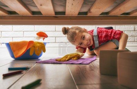 Photo pour Charmante petite assistante. Petite fille mignonne fait le ménage de la maison. Fille essuie le sol . - image libre de droit