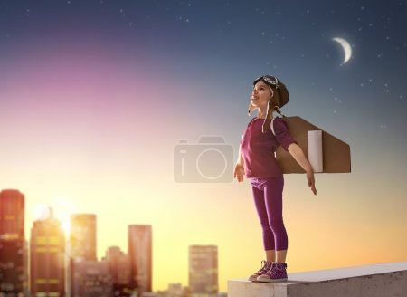 Photo for Little child girl plays astronaut. Child on the background of sunset sky. Child in an astronaut costume plays and dreams of becoming a spaceman. - Royalty Free Image