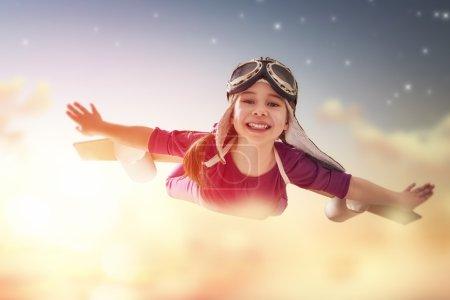 Photo pour Une petite fille joue les astronautes. Enfant sur le fond du ciel couchant. Enfant en costume d'astronaute joue et rêve de devenir un astronaute . - image libre de droit
