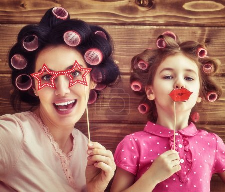 Photo for Funny family! Mother and her child daughter girl with a paper accessories. Beauty funny girl holding paper lips on stick. Beautiful young woman holding paper glasses on stick. - Royalty Free Image