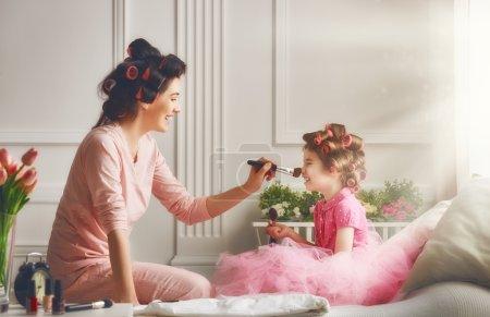 Photo pour Heureuse famille aimante. Mère et fille font les cheveux et s'amuser. Mère et fille faire votre maquillage assis sur le lit dans la chambre à coucher. - image libre de droit