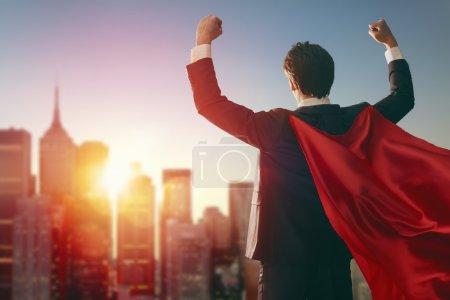 Foto de Empresario de superhéroe mirando puesta de sol en el horizonte de la ciudad. el concepto de éxito, el liderazgo y la victoria en el negocio. - Imagen libre de derechos