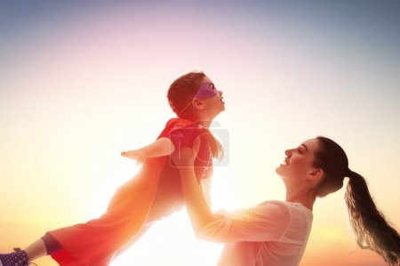 Photo for Mother and her child girl playing together. Girl in an Superhero's costume. - Royalty Free Image