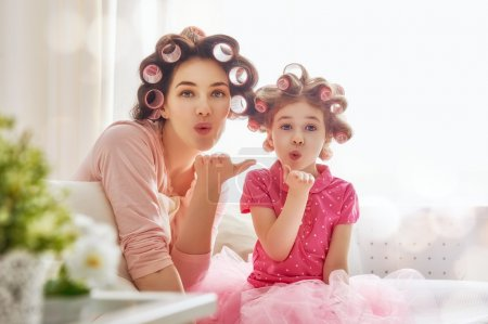 Photo for Happy loving family. Mother and daughter are doing hair and having fun. Mother and her child girl playing, kissing and hugging. - Royalty Free Image