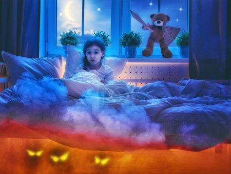 Photo pour Cauchemar pour les enfants. Petite fille enfant a peur des monstres dans l'obscurité de la nuit. Effrayé de petite fille et son ami ours en peluche sont protégés contre les monstres. - image libre de droit