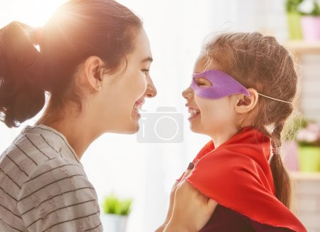 Photo for Happy family is preparing for a costume party. Mother and her child girl playing together. Girl in Superman's costume. - Royalty Free Image