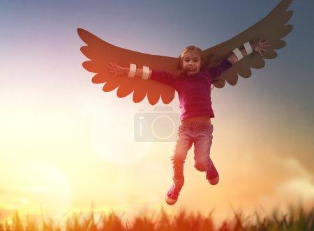 Photo pour La petite fille joue dehors. Enfant sur le fond du ciel couchant. Enfant avec les ailes d'un oiseau rêve de voler . - image libre de droit
