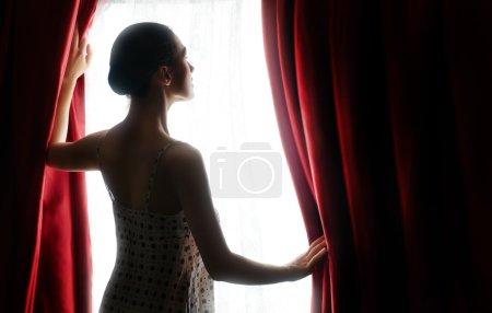 Photo pour Jolie femme ouvrant rideaux rouges - image libre de droit