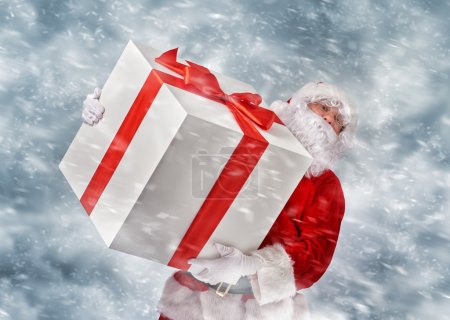 Photo for Santa Claus holding a huge Christmas gift. - Royalty Free Image