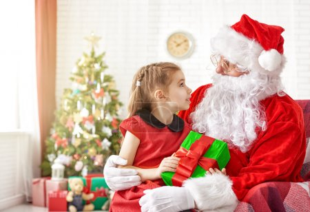 Photo for Santa Claus giving a present to a little cute girl - Royalty Free Image