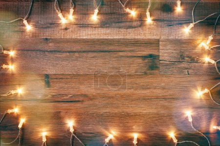Photo for Christmas garland lights on wooden rustic background. - Royalty Free Image
