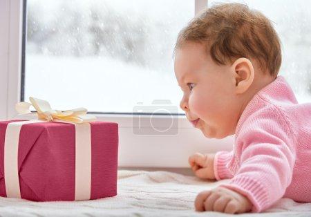Photo pour Petit bébé mignon regardant la boîte cadeau - image libre de droit