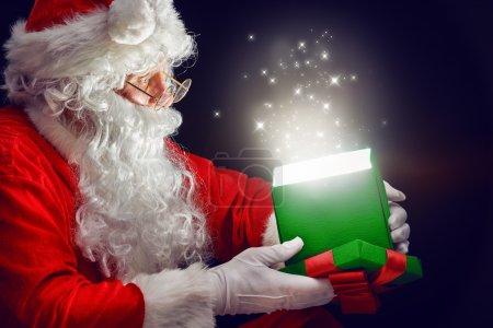 Photo for Santa Claus opening a magic gift box. - Royalty Free Image