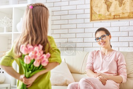 Photo for Cute little girl giving a bouquet of flowers to mother - Royalty Free Image