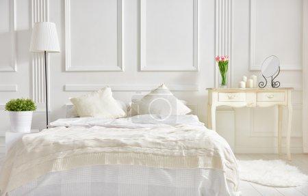Photo pour Chambre dans des couleurs douces et claires. grand lit double confortable dans une élégante chambre classique - image libre de droit