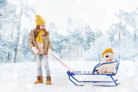 Photo for Happy child girl plaing with a toy on a snowy winter walk. child rolls a teddy bear on a sled - Royalty Free Image