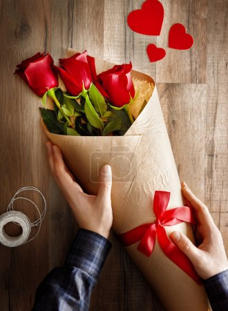 Photo for Male hands holding red roses on wooden background. the concept of love and Valentine's day. - Royalty Free Image