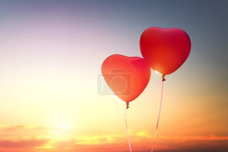 Photo pour Deux ballons rouges en forme de cœur sur le fond du ciel couchant. le concept d'amour et la Saint-Valentin . - image libre de droit