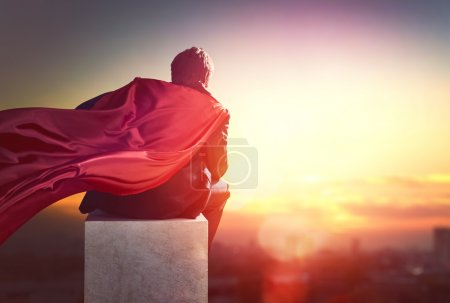 Photo for Superhero businessman looking at city skyline at sunset. the concept of success, leadership and victory in business - Royalty Free Image