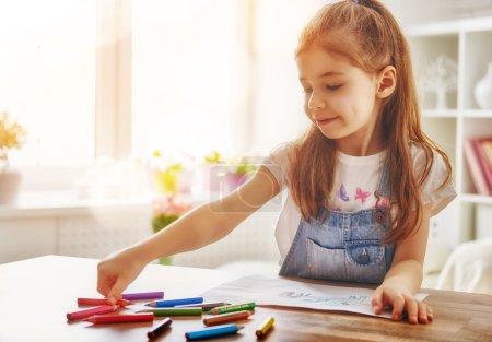 Photo pour Un enfant heureux joue. Petite fille enfant dessine avec des crayons de couleur . - image libre de droit