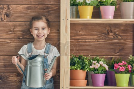 Photo for Cute child girl caring for her plants. Girl watering flowers in pots. Spring concept, nature and care. - Royalty Free Image