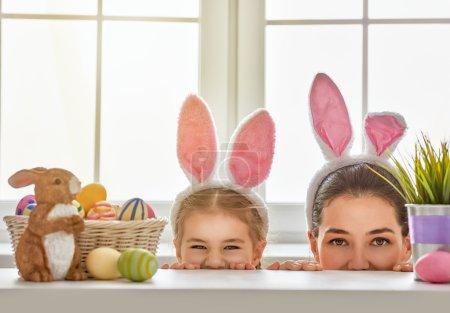 Photo pour Joyeux Pâques ! Mère et fille commencent à chasser les œufs de Pâques. Bonne famille se préparant pour Pâques. Petite fille mignonne portant des oreilles de lapin le jour de Pâques . - image libre de droit