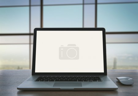 Photo for Laptop with blank screen on table in office - Royalty Free Image