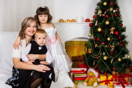 Photo pour Happy mother and two her children near an decorated fir-tree for Christmas - image libre de droit