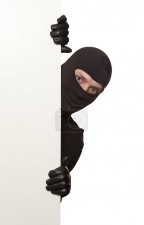 Ninja. Robber hiding behind a empty white sign wit...