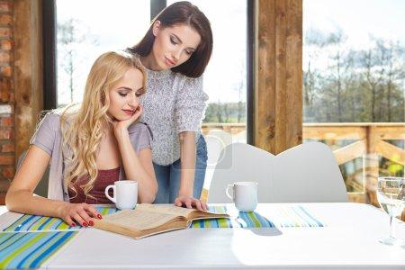 Photo pour Deux femmes s'assoient sur la table avec des tasses à la maison - image libre de droit
