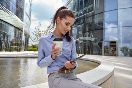 woman drinking coffee and reading tablet