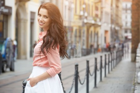 pretty trendy girl posing at city