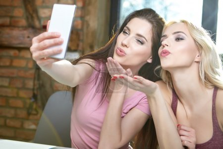 Photo for Two girls taking pictures on the phone at home - Royalty Free Image