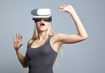 Photo pour Femme utilisant le casque de réalité virtuelle et gesticuler les mains en studio - image libre de droit