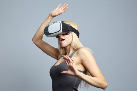 Photo for Woman using the virtual reality headset and gesticulating hands in studio - Royalty Free Image